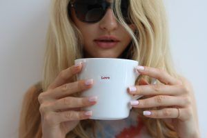 Pink manicure girl holding mug